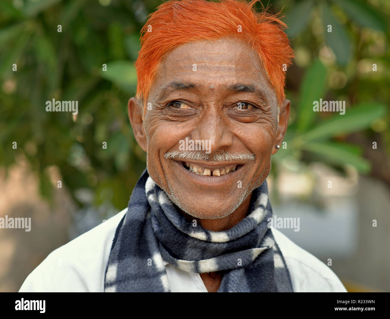 Squinting, middle-aged Indian man (right eye deviated outward) with a pencil moustache and henna-dyed orange hair smiles for the camera. - Stock Image