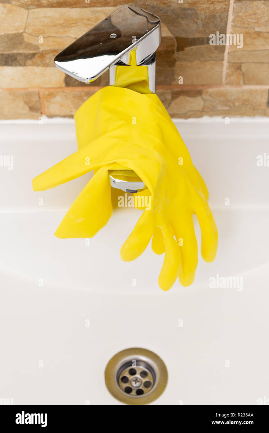 Yellow rubber hygienic gloves hanging on inox water tap - Stock Image