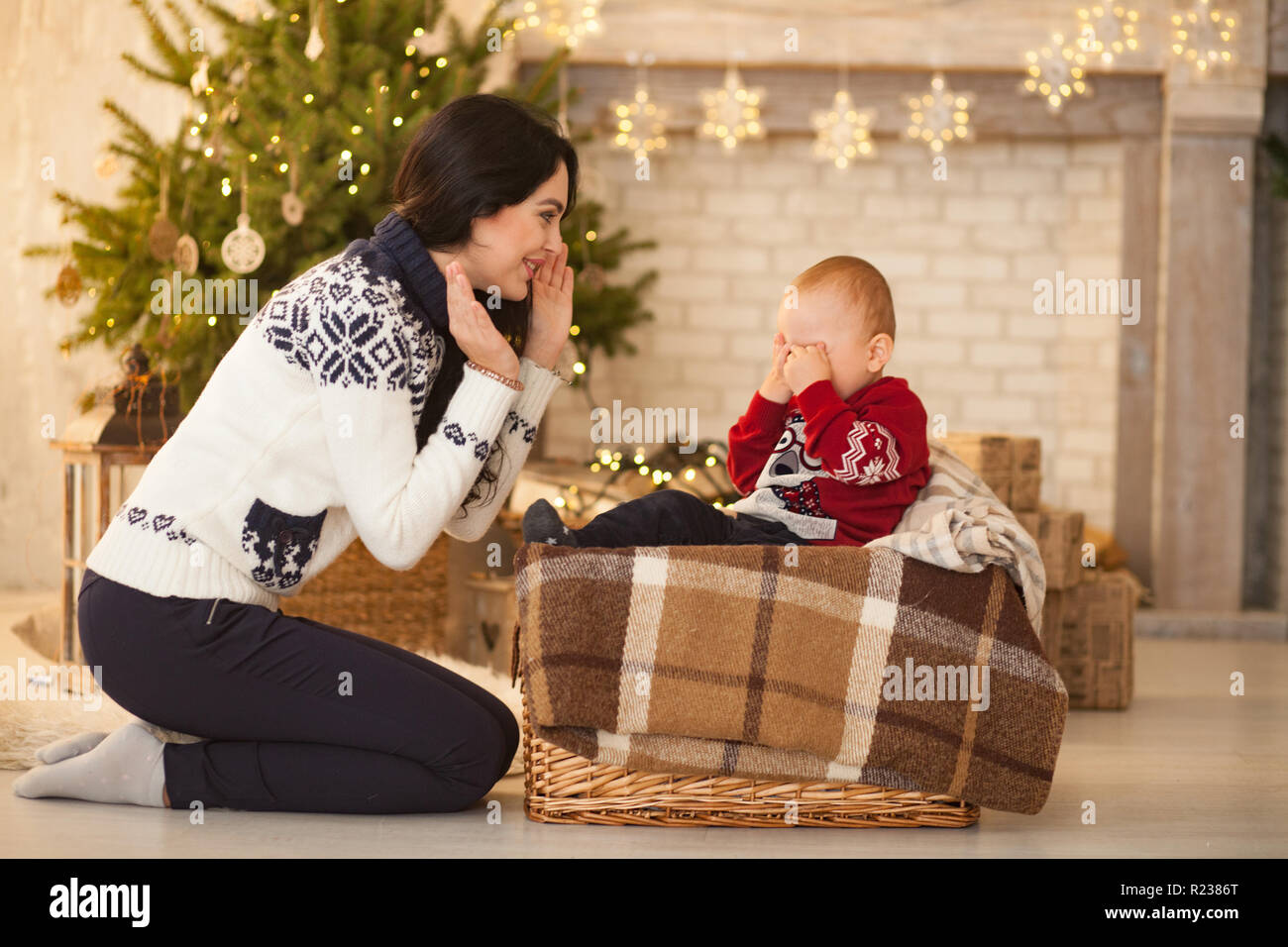 Mother comforts her little crying son on background of the Christmas tree and festive garlands. Stock Photo