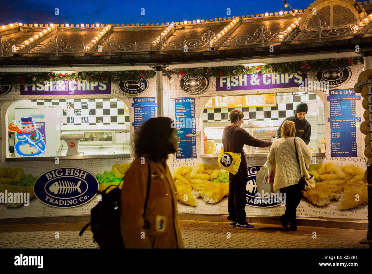 At a fish-and-chip stall on Brighton Pier a young man and woman are buying food. Overhead the roof has rows of light bulbs under an evening sky. Stock Photo