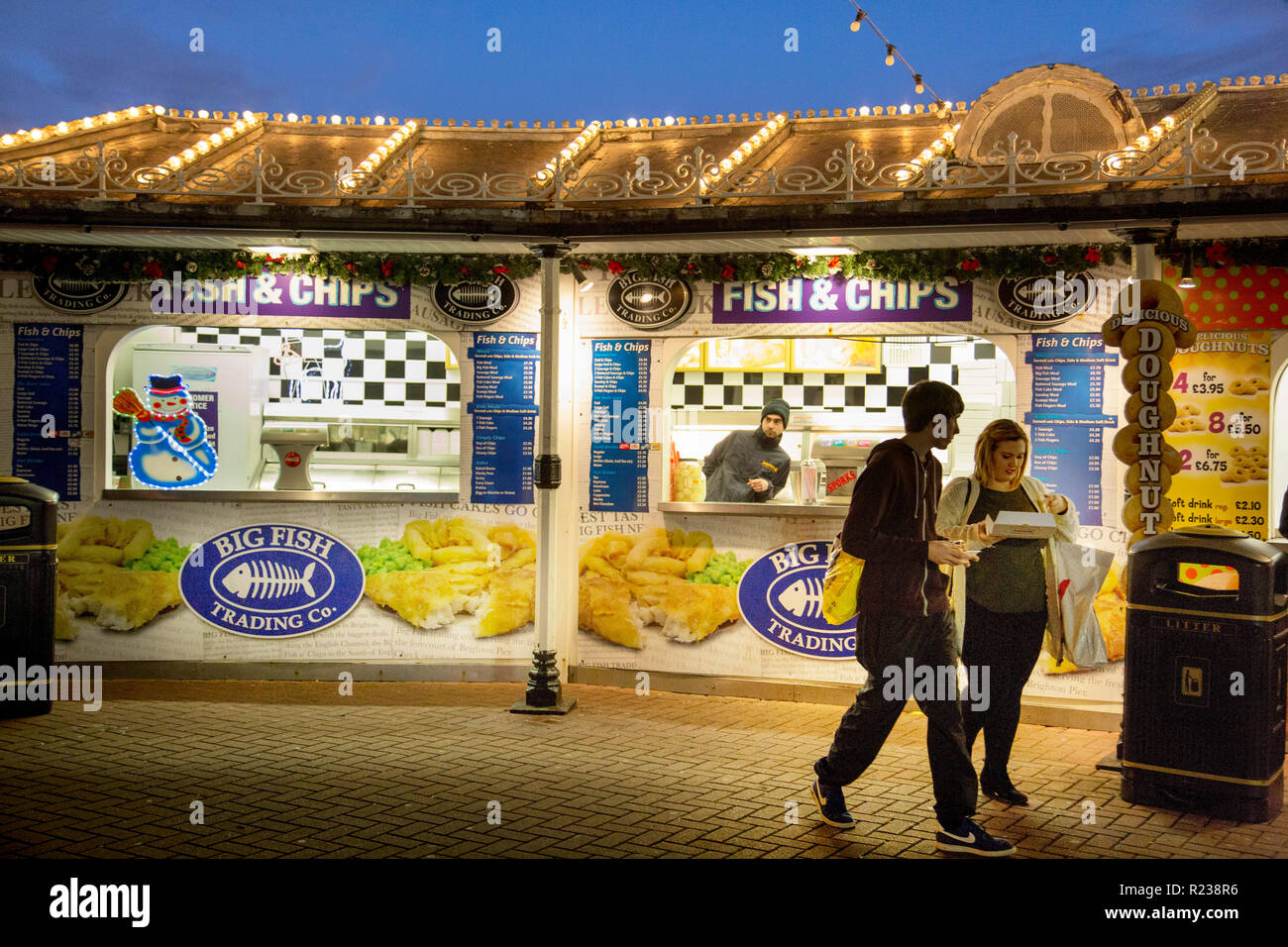 At a fish-and-chip stall on Brighton Pier a young man and woman are buying food. Overhead the roof has rows of light bulbs under an evening sky. - Stock Image