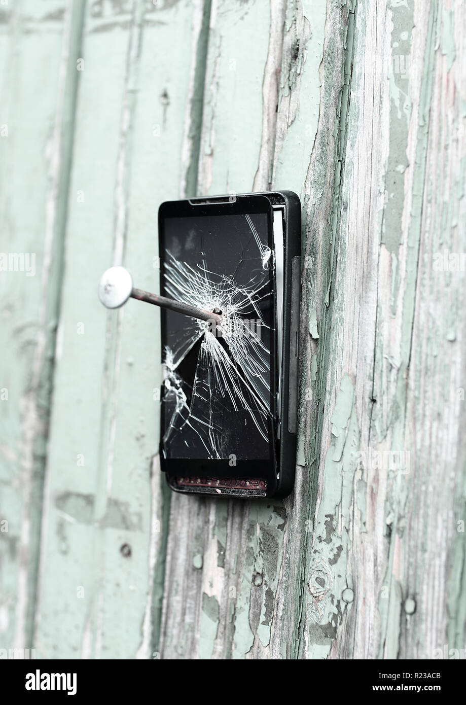 obsolete mobile phone is nailed to a wooden fence - Stock Image