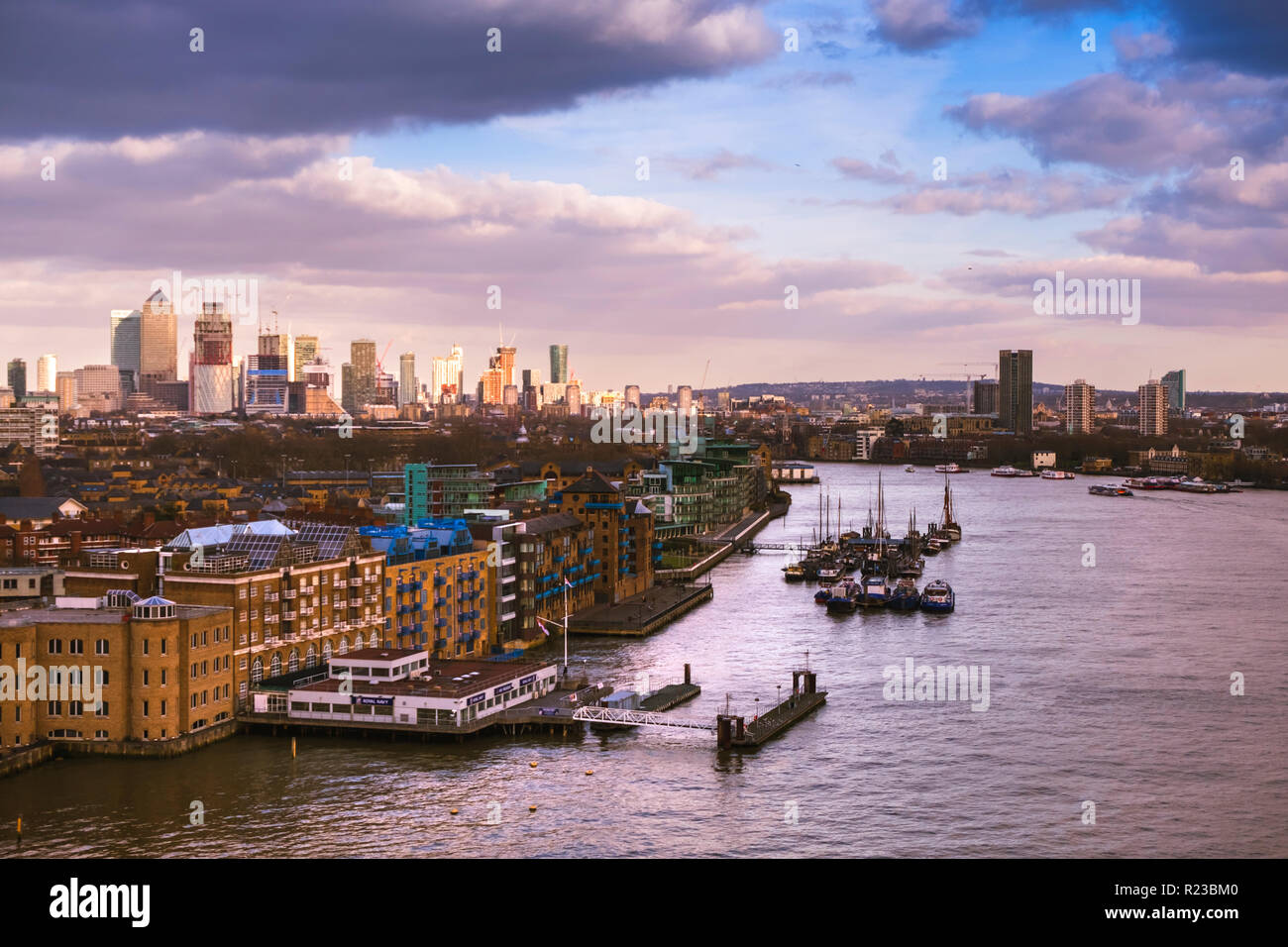 London skyline in sunset light. View towards the docklands and skyscrapers seen from the Tower Bridge in sunset light - Stock Image