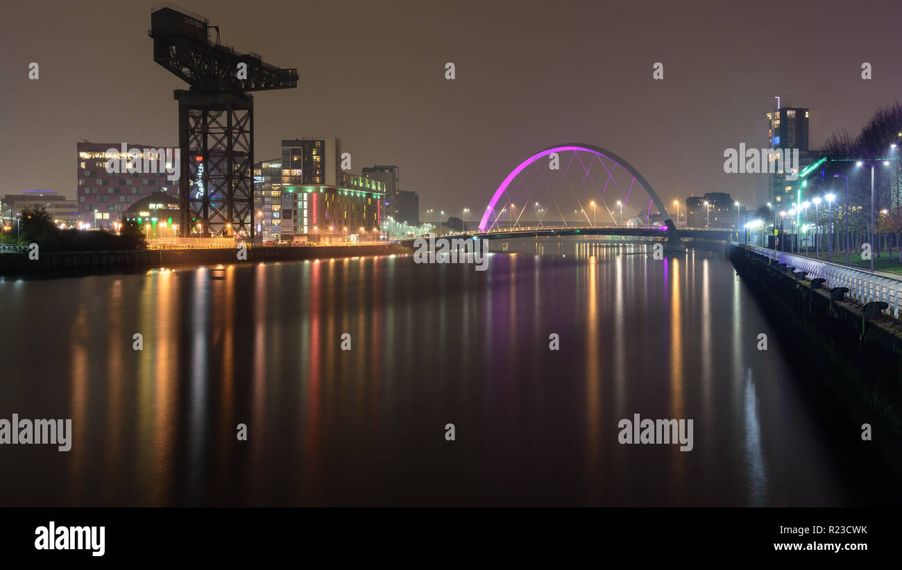 Glasgow, Scotland, UK - November 5, 2018: The River Clyde flows under the Clyde Arc bridge and past the landmark Finnieston Crane at night in Glasgow. - Stock Image