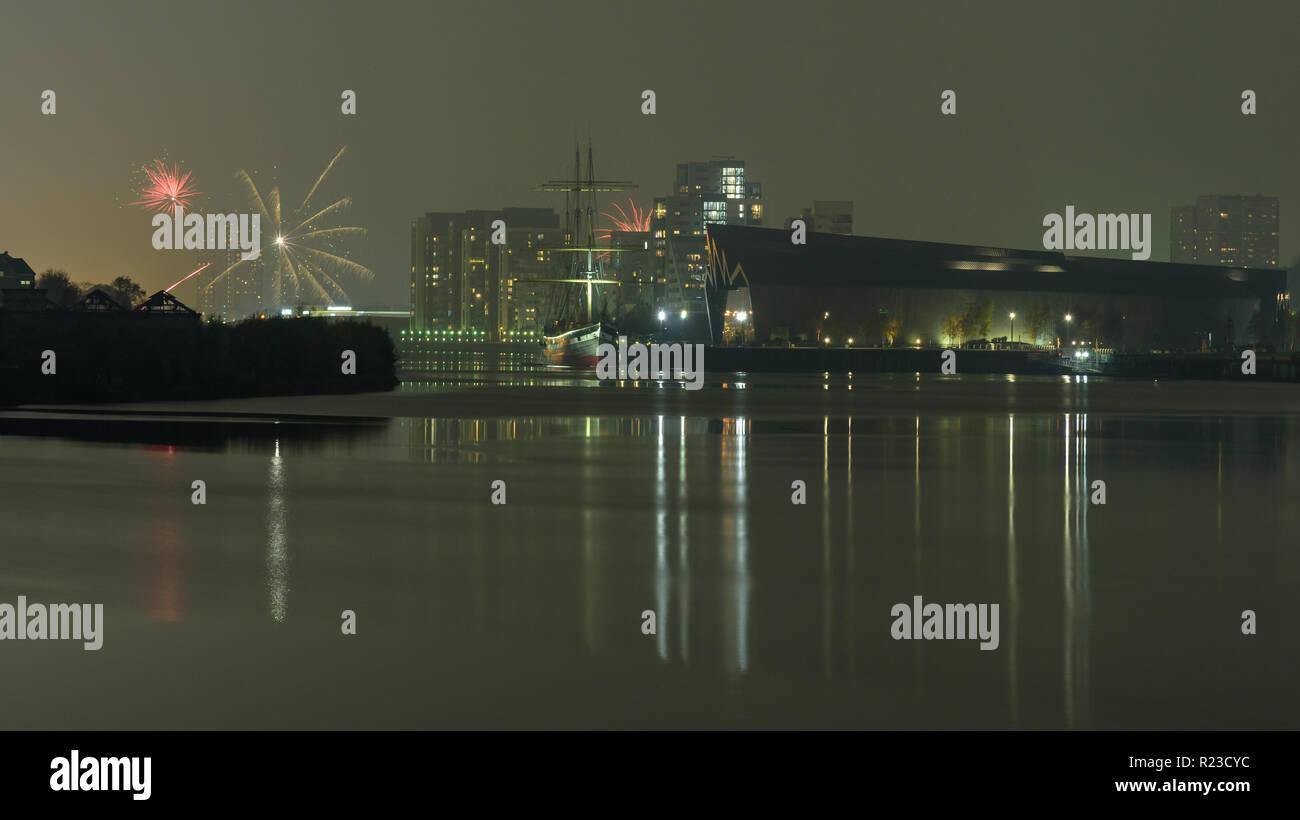 Glasgow, Scotland, UK - November 5, 2018: Fireworks explode above apartment buildings in Partick, beside the modernist Riverside Museum and Glenlee ta - Stock Image