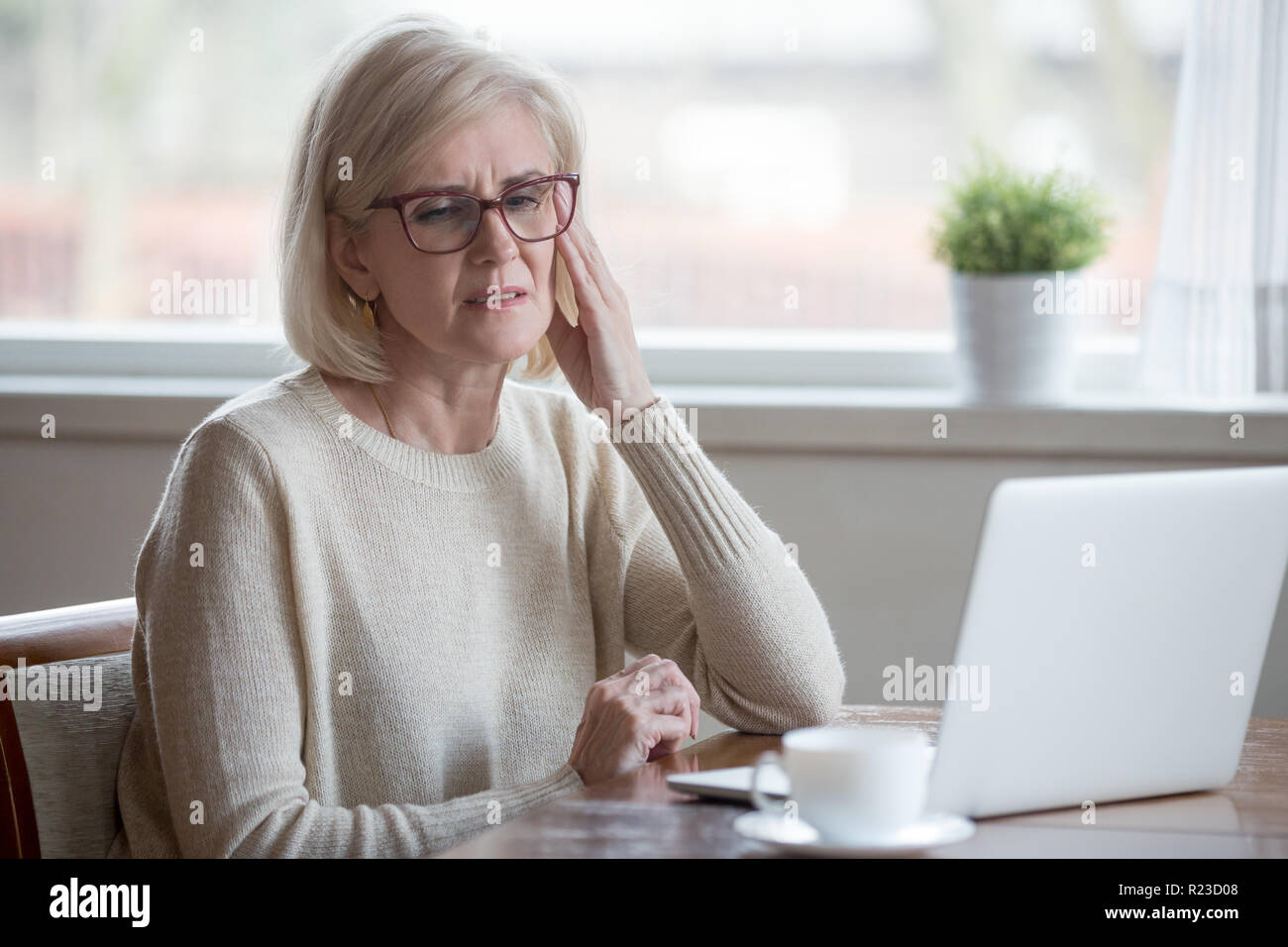 Upset aged woman using laptop at home suffering from headache, tired senior female massaging temples having severe pain or blurry vision, exhausted el Stock Photo