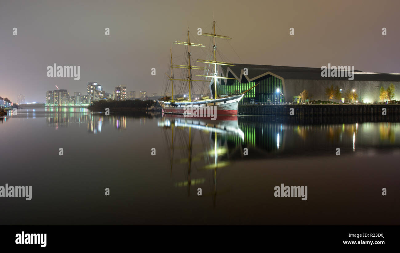 Glasgow, Scotland, UK - November 5, 2018: The Clyde-built tall ship Glenlee is lit at night outside the Riverside Museum of Transport in the Partick n - Stock Image