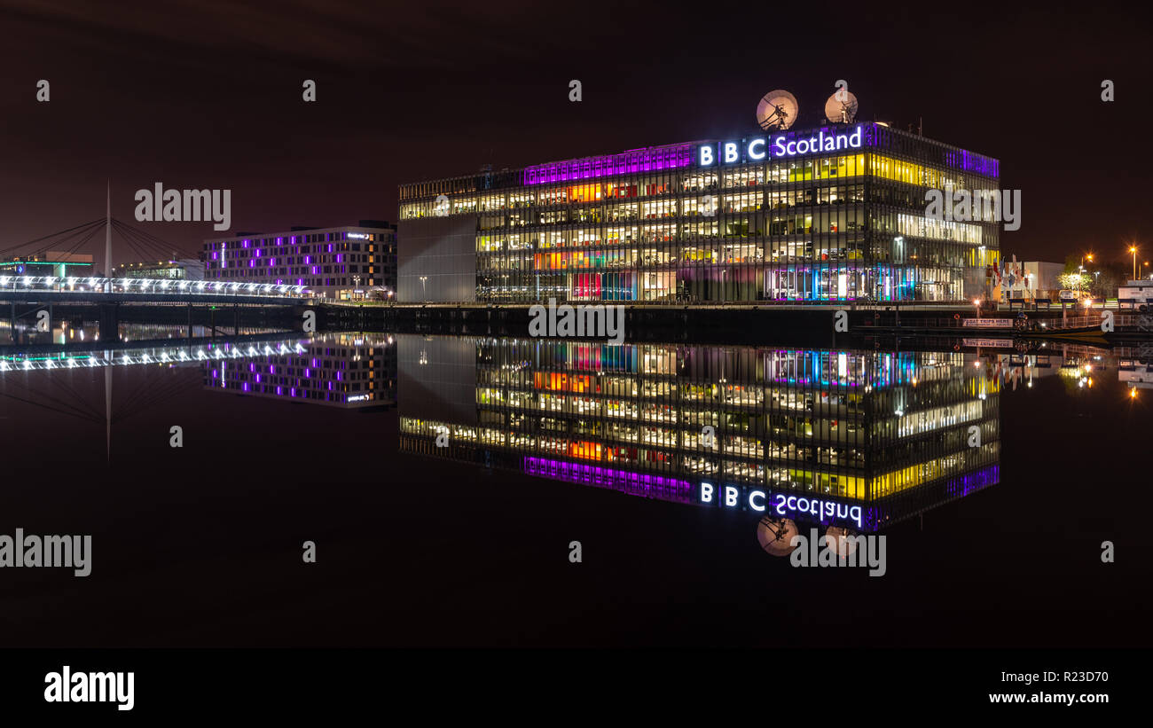 Glasgow, Scotland, UK - November 4, 2018: The modern offices and studios of BBC Scotland at lit at night and reflected in the waters of the River Clyd - Stock Image