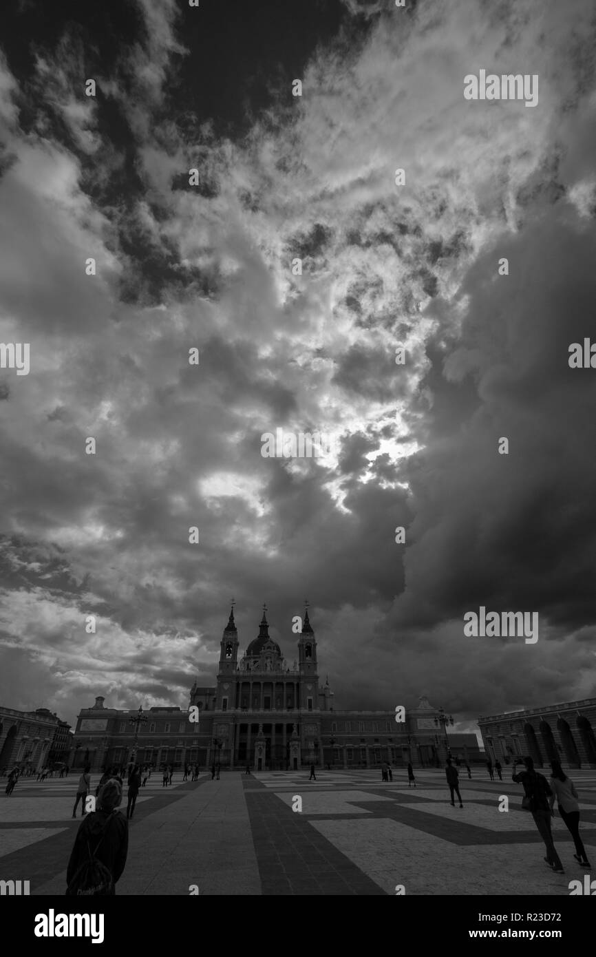 Dark stormy skies over the Cathedral of Almudena, catedral de la Almudena in black and white, seen from the Royal Palace in Madrid, Spain - Stock Image