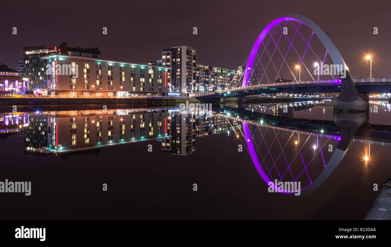 Glasgow, Scotland, UK - November 4, 2018: Modern apartment buildings are reflected in the River Clyde beside the Clyde Arc bridge in Glasgow at night. Stock Photo