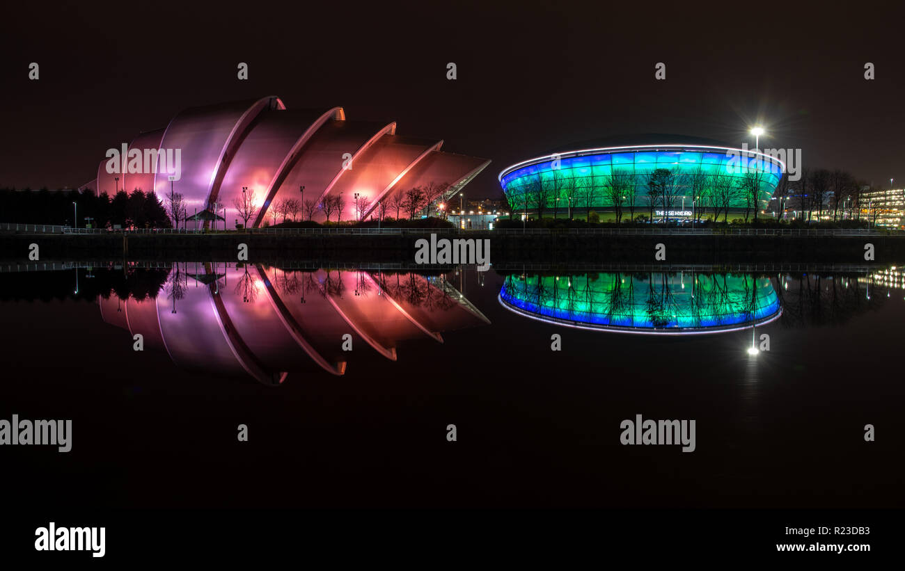 Glasgow, Scotland, UK - November 4, 2018: The modernist SEC Armadillo auditorium and SSE Hydro arena are lit at night and reflected in the River Clyde - Stock Image