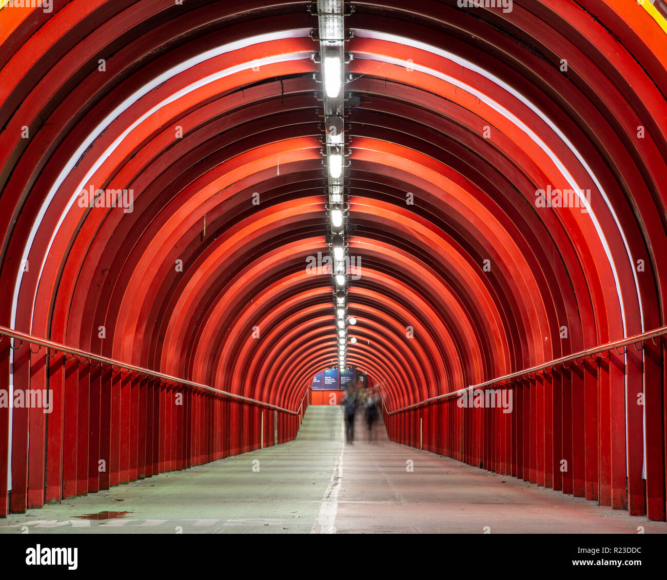 Glasgow, Scotland, UK - November 4, 2018: Pedestrians walk through a bright red covered walkway linking the Scottish Event Campus to Exhibition Centre - Stock Image