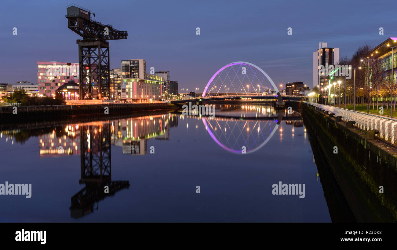 Glasgow, Scotland, UK - November 4, 2018: The modern Clyde Arc bridge is lit at night across the River Clyde beside the iconic Finnieston Crane in Gla Stock Photo