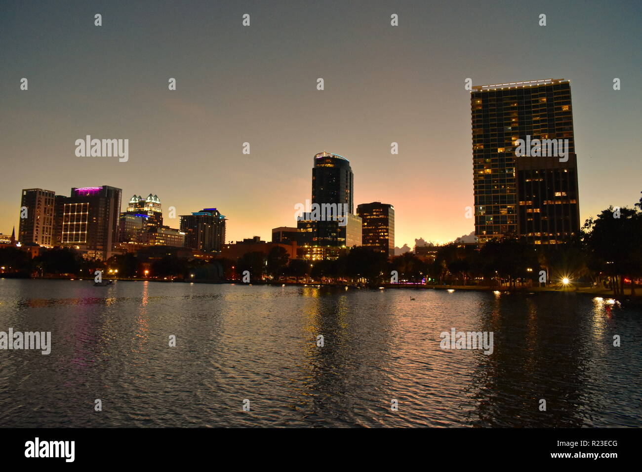 Orlando, Florida. October 16, 2018 Iluminated Downtown Buildings on magenta sunset at Eola Lake Park area. - Stock Image