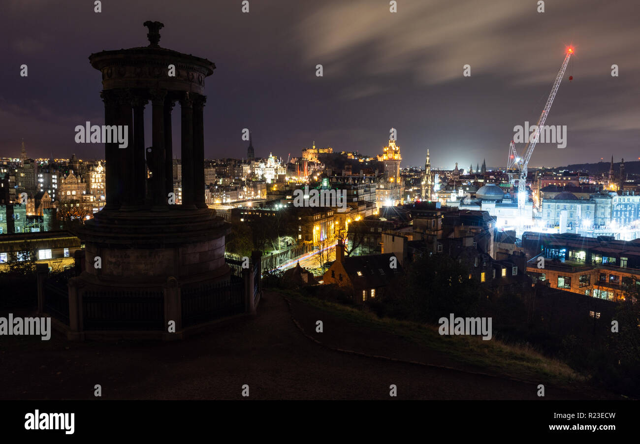 Edinburgh, Scotland, UK - November 2, 2018: Streets and landmarks in the city of Edinburgh are lit up at night behind the Dugald Stewart Monument in C - Stock Image