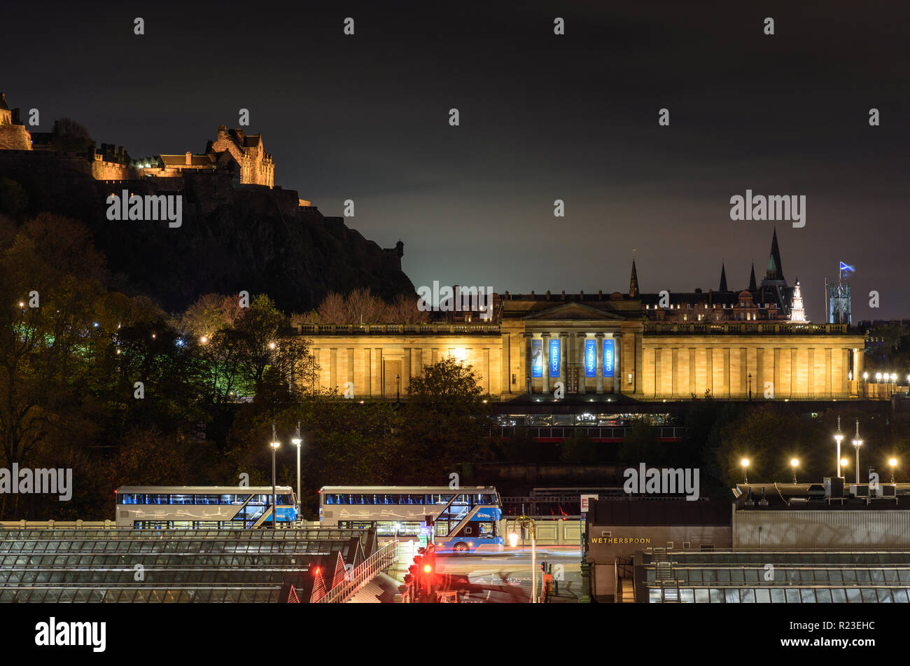 Edinburgh, Scotland, UK - November 2, 2018: The National Gallery of Scotland and Edinburgh Castle are lit at night above the glass roof of Waverley Ra - Stock Image