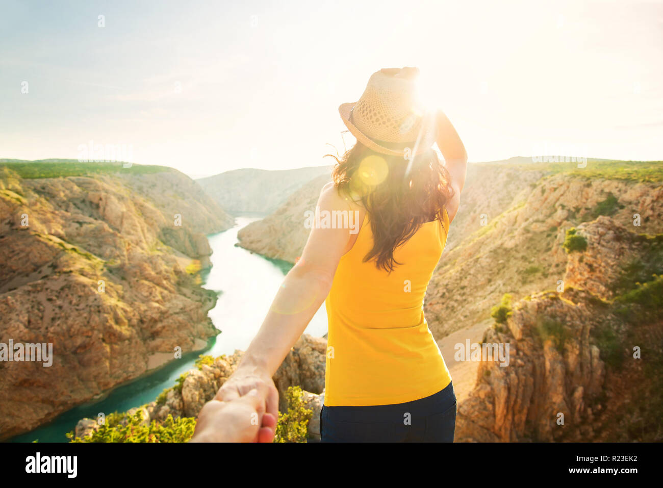 young woman in yellow top and hat standing with her back to camera at edge of cliff looking at sunset over Zrmanja river canyon, Zadar, Croatia Stock Photo