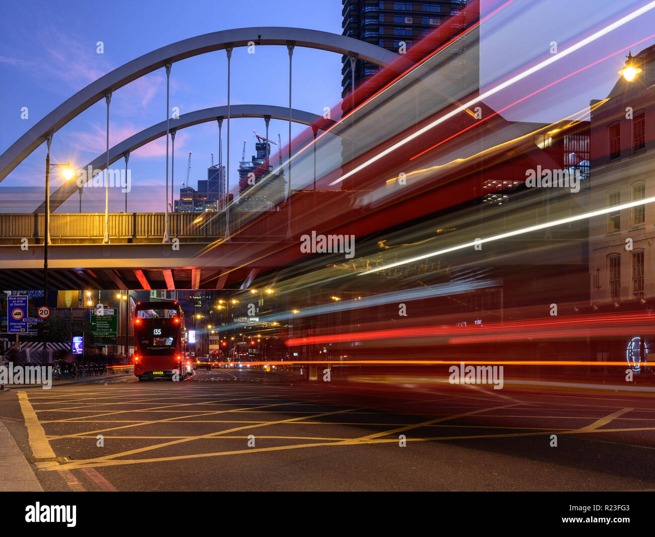 London, England, UK - October 20, 2018: Red double-decker buses leave light trails as they move along Shoreditch High Street, under London Overground' Stock Photo