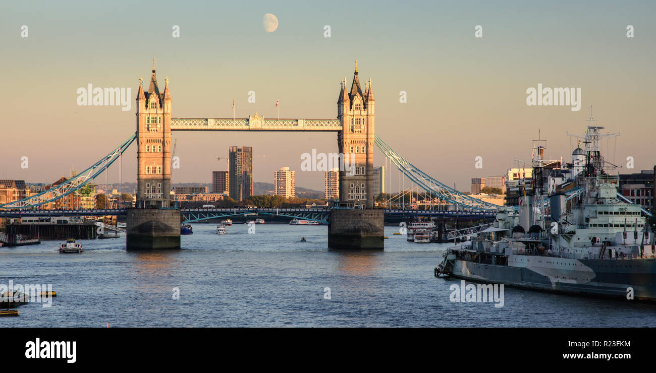 London, England, UK - October 20, 2018: The moon rises over London's iconic Tower Bridge against a backdrop of air pollution. - Stock Image