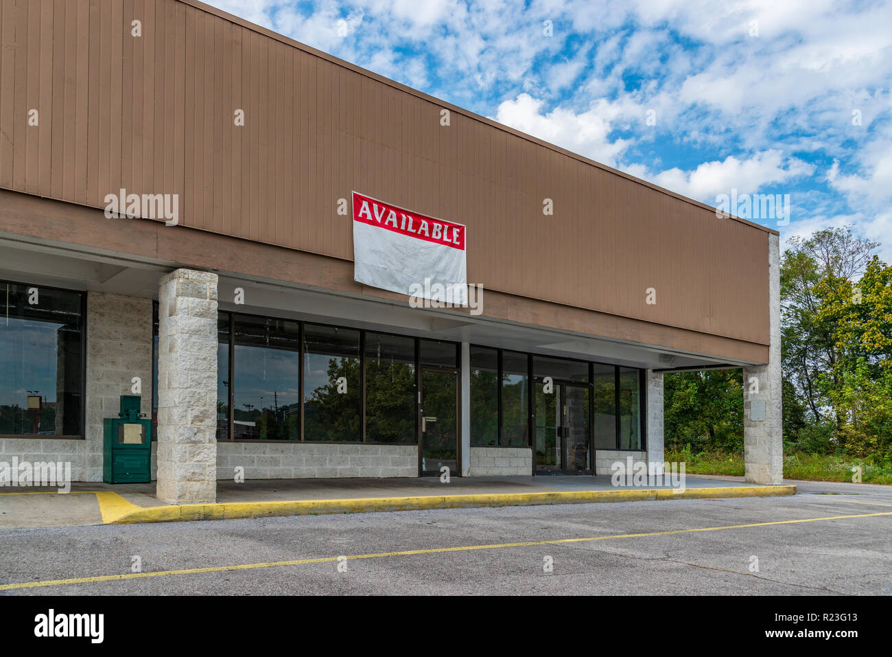 Sevierville, TN / United States - October 15, 2018: Horizontal shot of Available Retail Space in an Older Strip Shopping Center under a blue cloudy sk - Stock Image