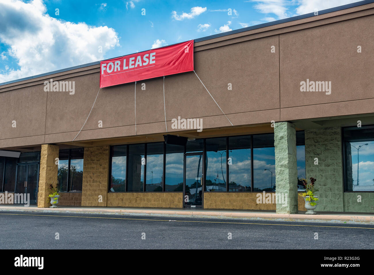 Sevierville, TN / United States - October 15, 2018: Horizontal shot of Retail Space Available in an old strip shopping center under a blue cloudy sky. - Stock Image