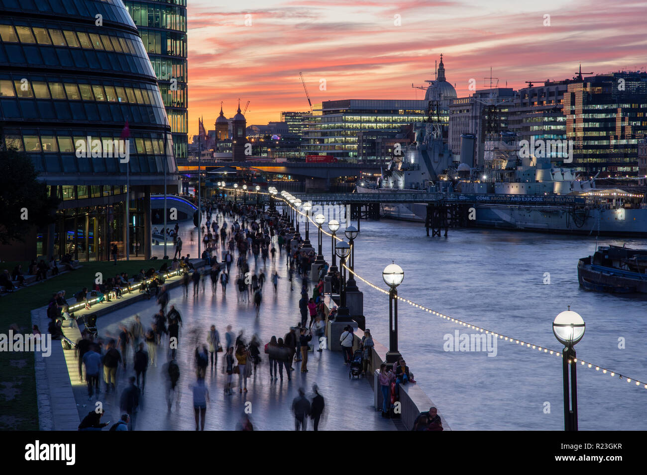 London, England, UK - September 27, 2018: Pedestrians and tourists walk along the River Thames Path beside City Hall and HMS Belfast at sunset. Stock Photo