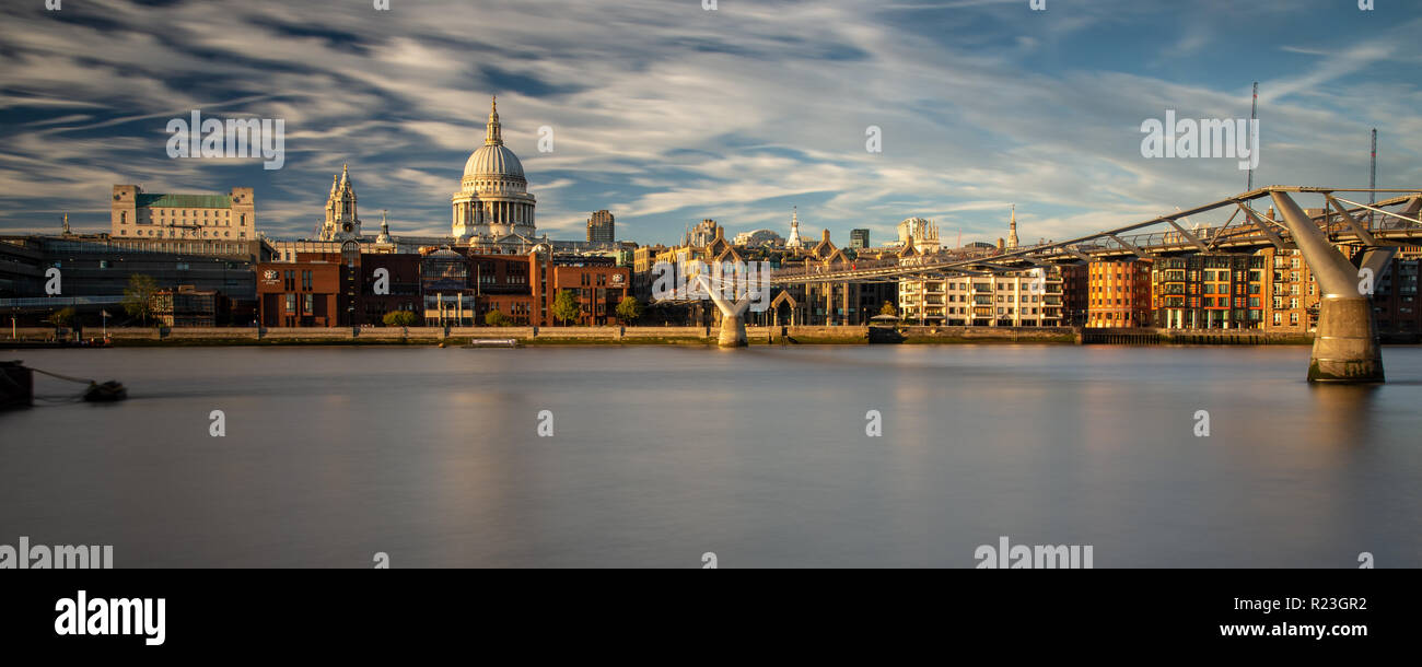London, England, UK - September 27, 2018: Evening sun illuminates the dome of St Paul's Cathedral and the Millennium Bridge on the River Thames in the Stock Photo