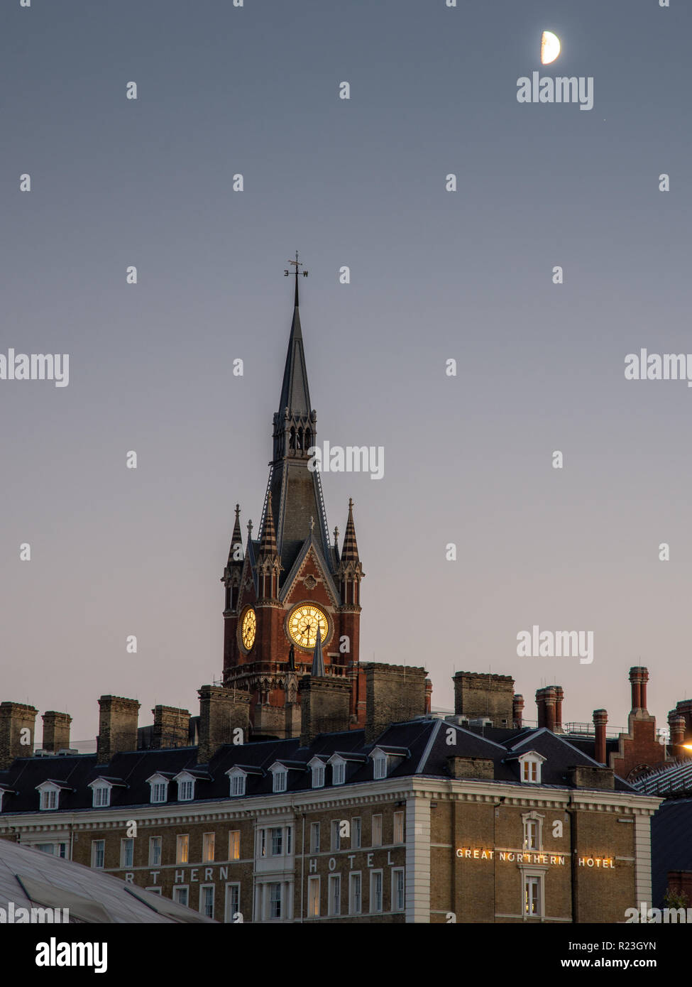 London, England, UK - September 17, 2018: A half moon rises above the gothic spire of St Pancras International Railway Station and Great Northern Hote Stock Photo