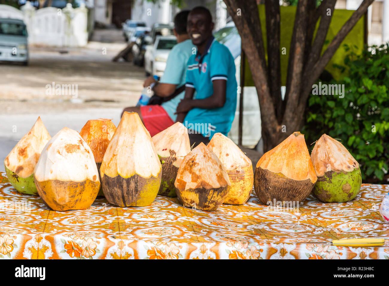 Street vendor of coconuts. Stone Town, old colonial center of Zanzibar City, Unguja island, Tanzania - Stock Image