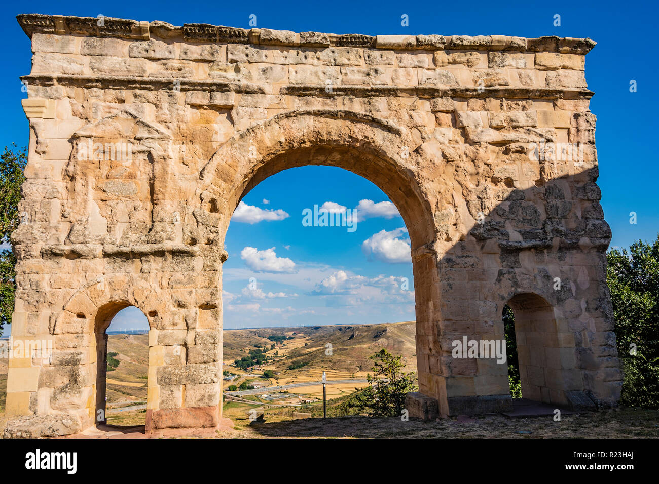 Close-up of Roman arch and back the village of Medinaceli. Soria Spain. - Stock Image