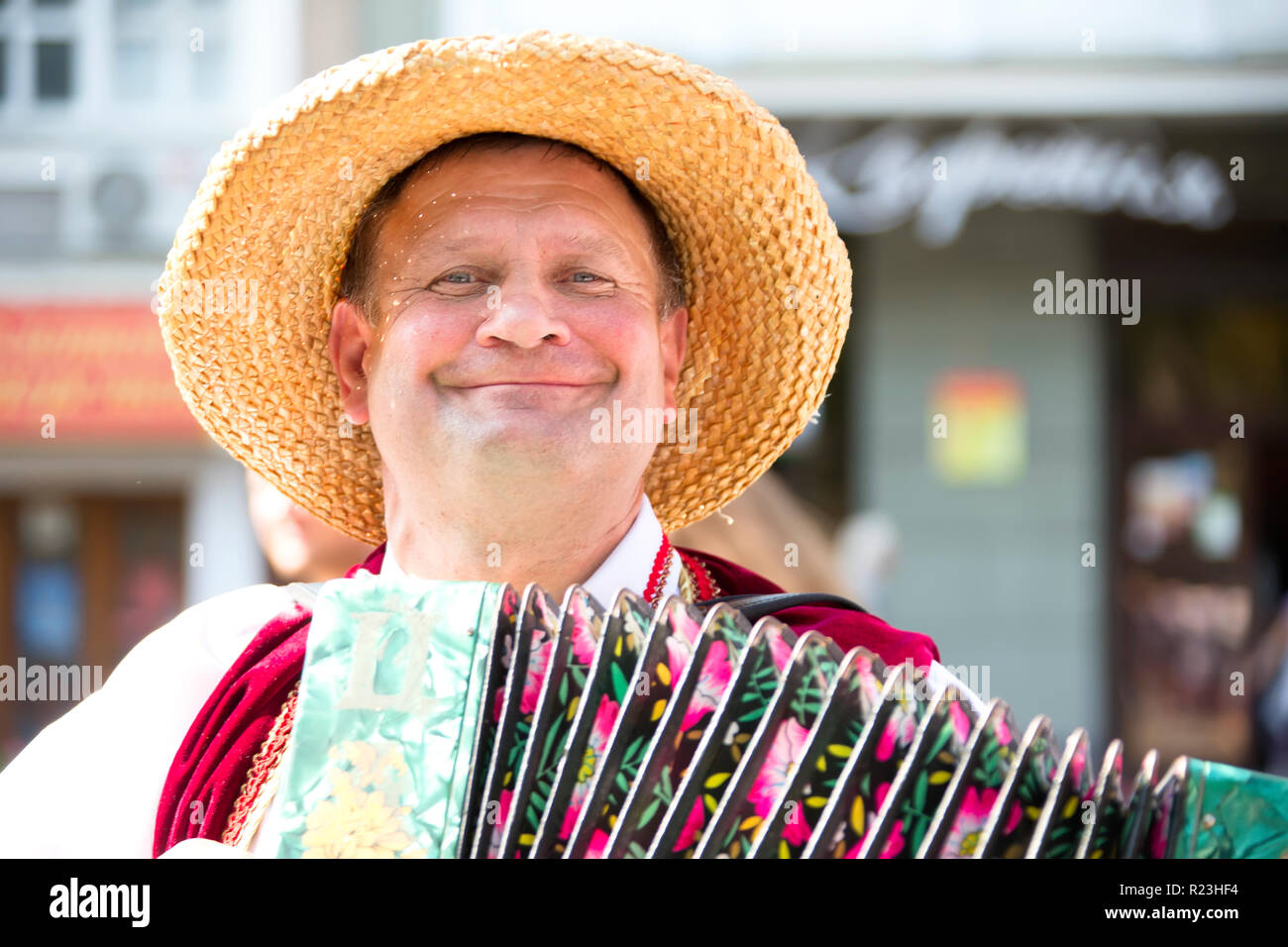 .A man in a straw hat playing the harmonica.Harmonist - Stock Image
