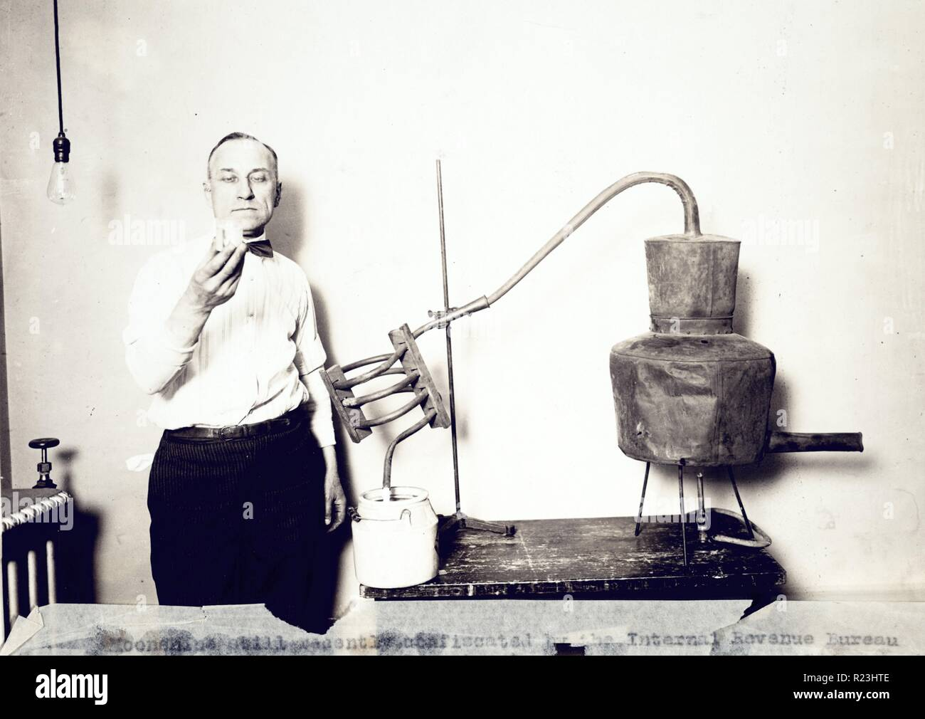 Moonshine still recently confiscated by the Internal Revenue Bureau photographed at the Treasury Department. Man standing next to still looking at contents of glass. 1921 - Stock Image