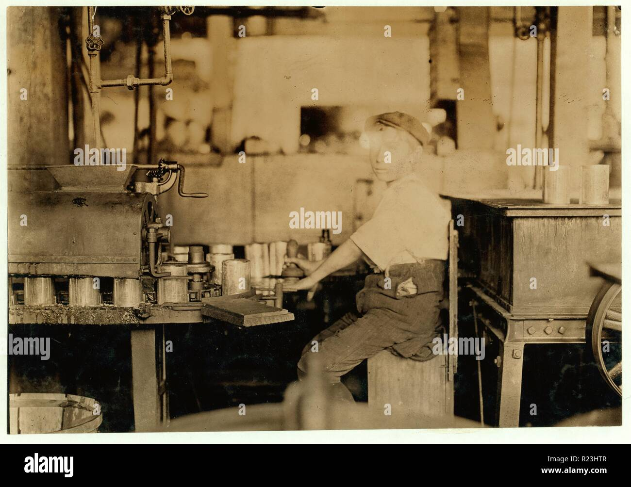 Dangerous Business. Boy working at canning machine with open gearing. J. S. Farrand Packing Co. July 7, 1909. Location: Baltimore, Maryland. 1909 - Stock Image
