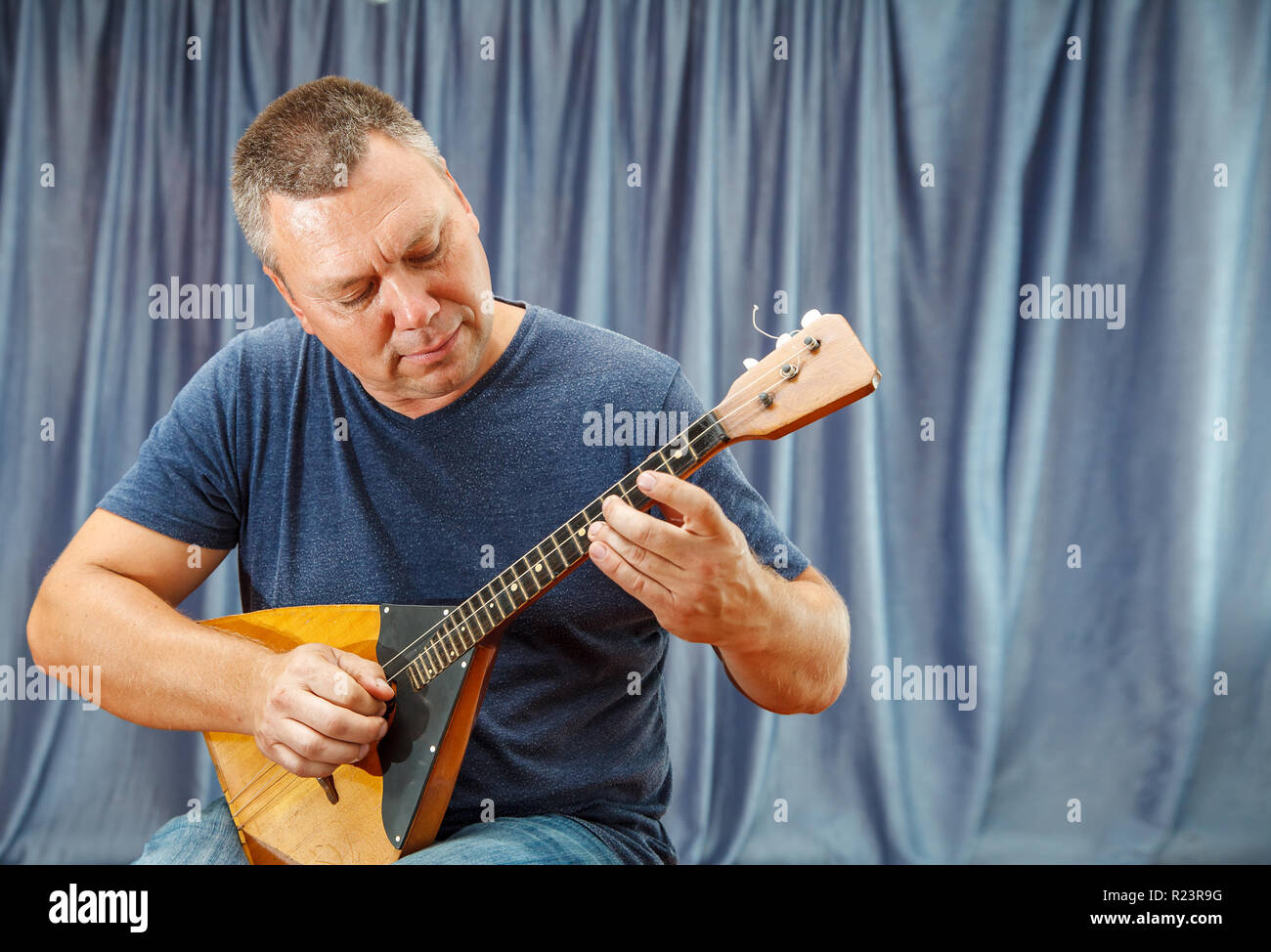 elderly man playing the balalaika indoor with bright daylight - Stock Image