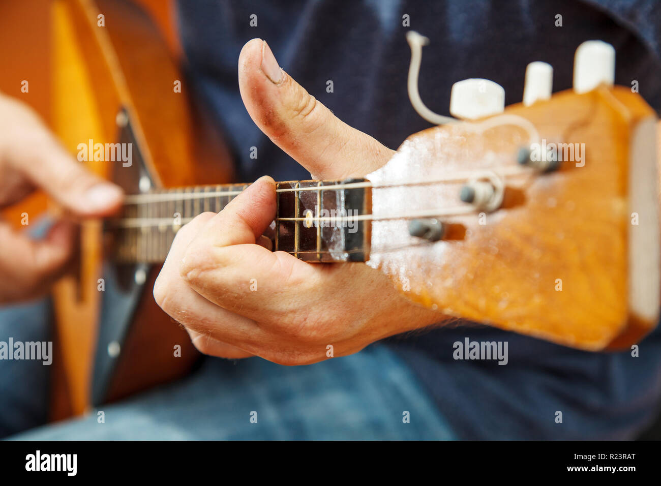 man playing the balalaika indoor with bright daylight. hands closeup - Stock Image