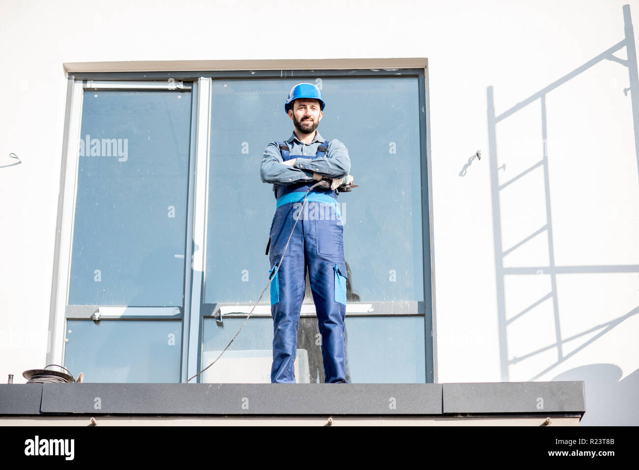 Portraiit of a builder in uniform standing on the balcony of a new house on the construction site Stock Photo