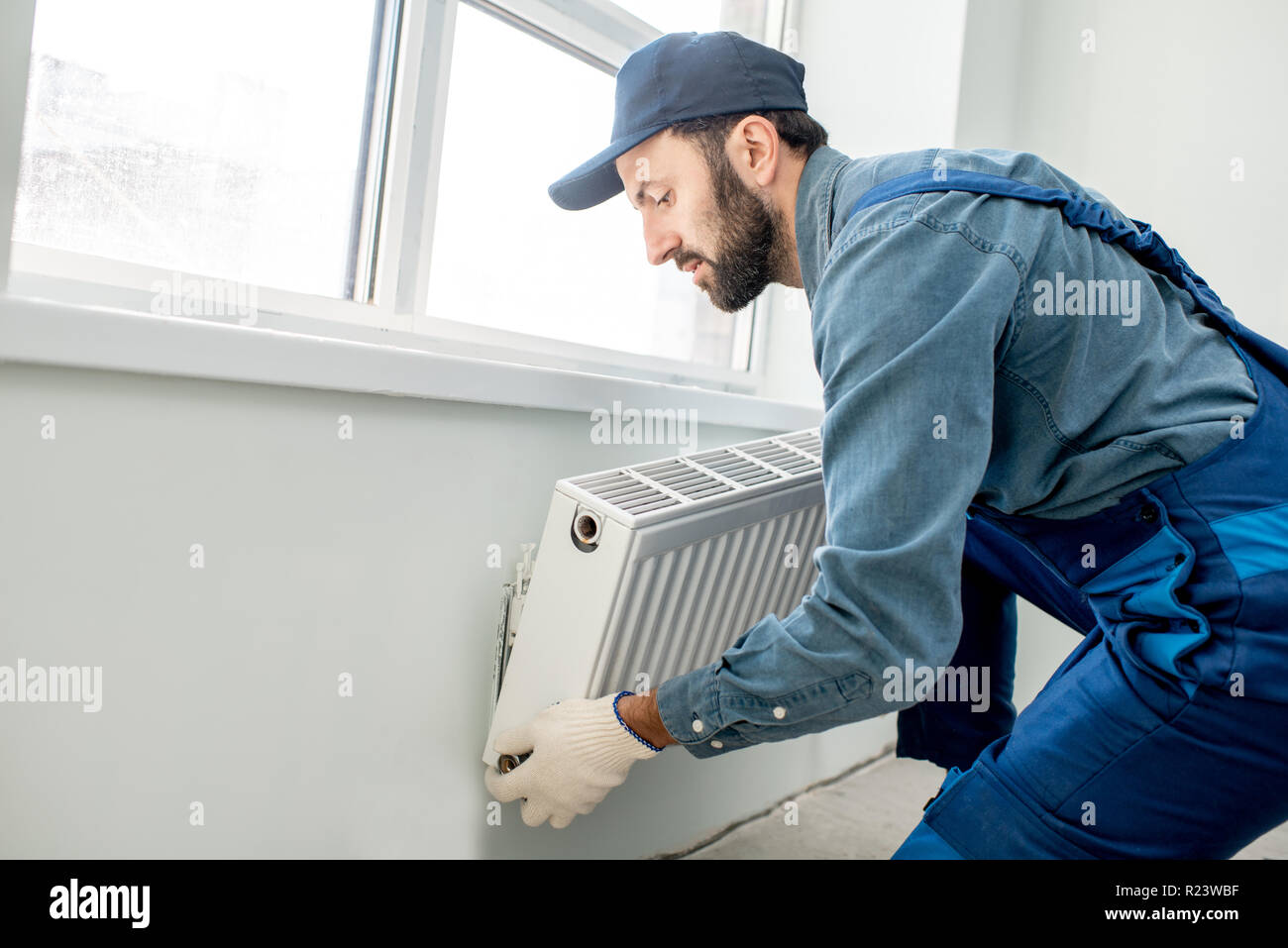 Workman mounting water heating radiator near the window in the white renovated living room - Stock Image