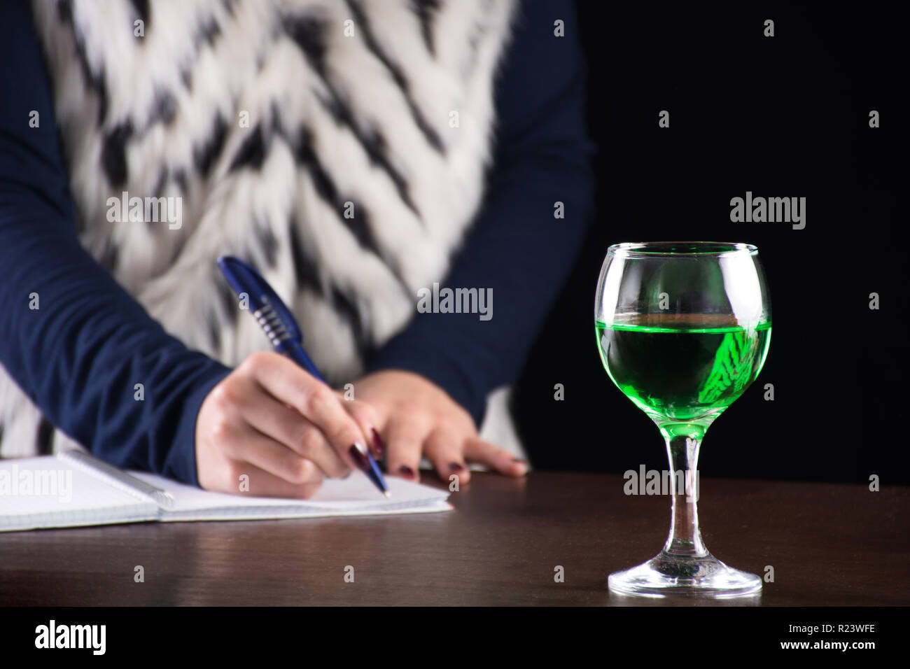 Absinthe green drink in glass and woman writing story notebook in background on old retro wooden desk. Green fairy inspiration and muse for writer - Stock Image