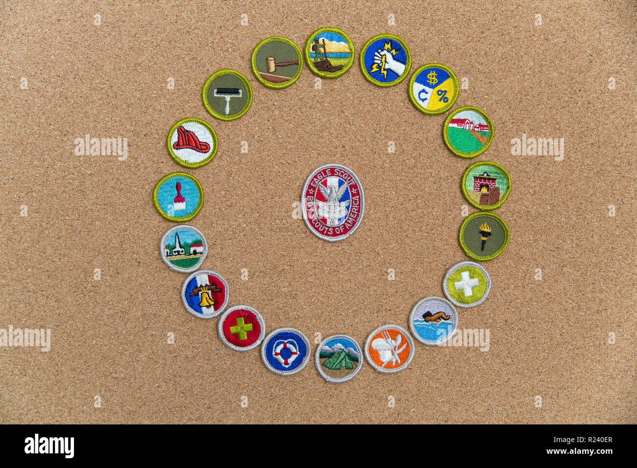 SAINT LOUIS, UNITED STATES - AUG 22, 2018:  A circular arrangement of Boy Scouts of America (BSA) merit badges with Eagle badge on cork background - Stock Image