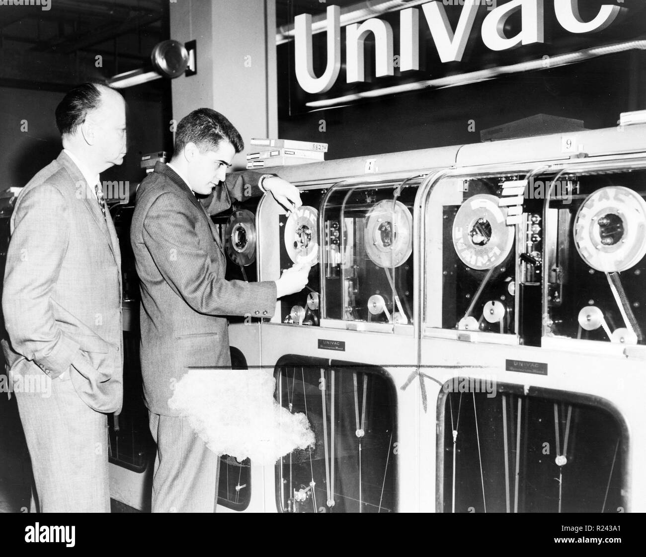 One man looks on as another man prepares Univac computer to predict a winning horse in a race c.1955 - Stock Image
