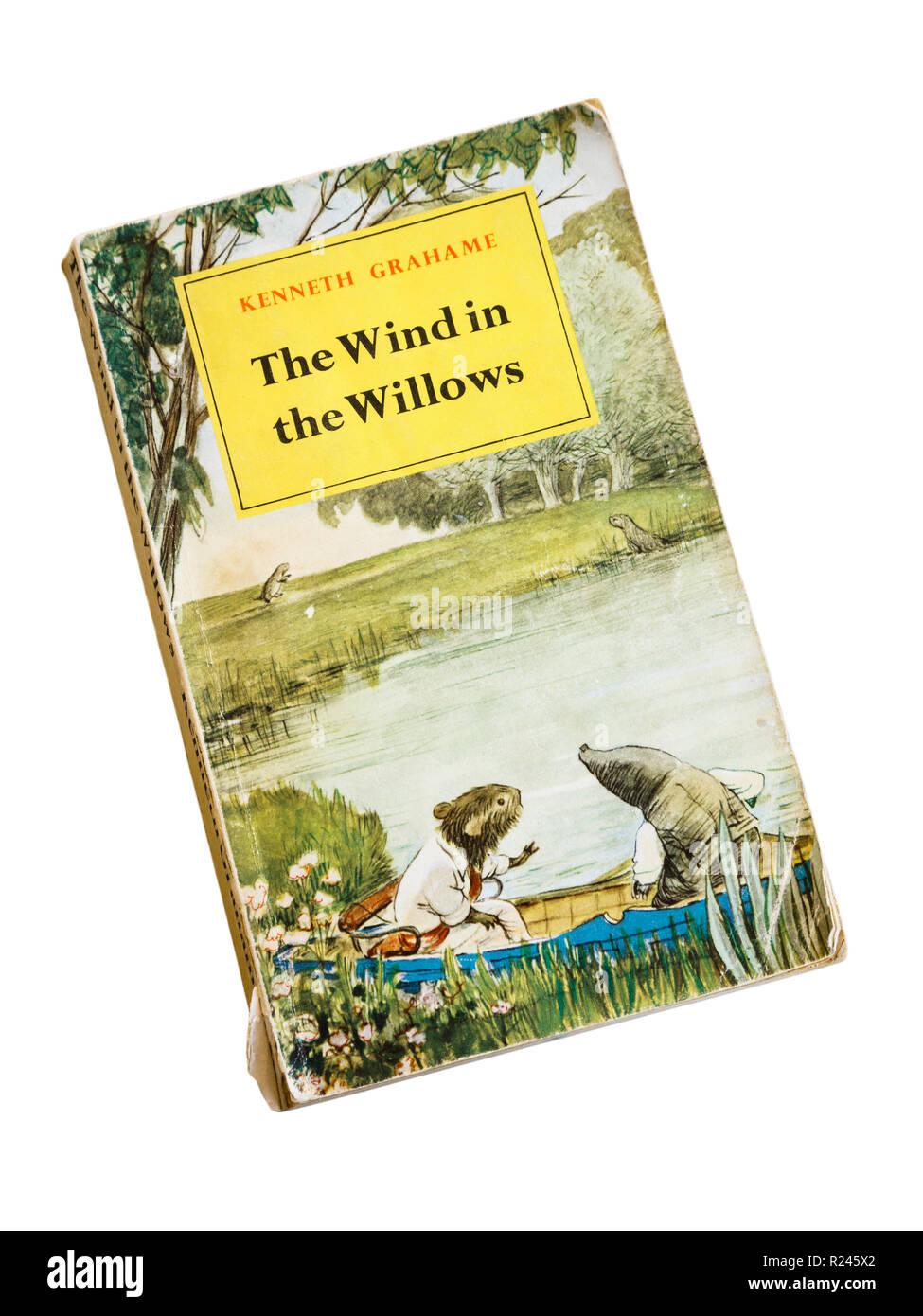 Illustrated front cover of old dog-eared paperback book The Wind in the Willows by Kenneth Grahame. Cutout on white. 1961 edition by Methuen & Co Ltd. - Stock Image