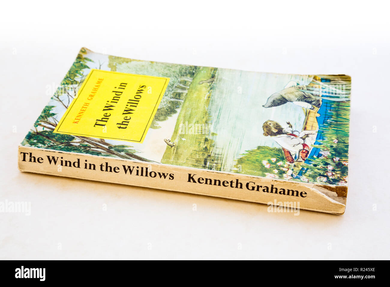 Illustrated front cover of old dog-eared paperback book with torn spine, The Wind in the Willows by Kenneth Grahame. 1961 edition by Methuen & Co Ltd. - Stock Image