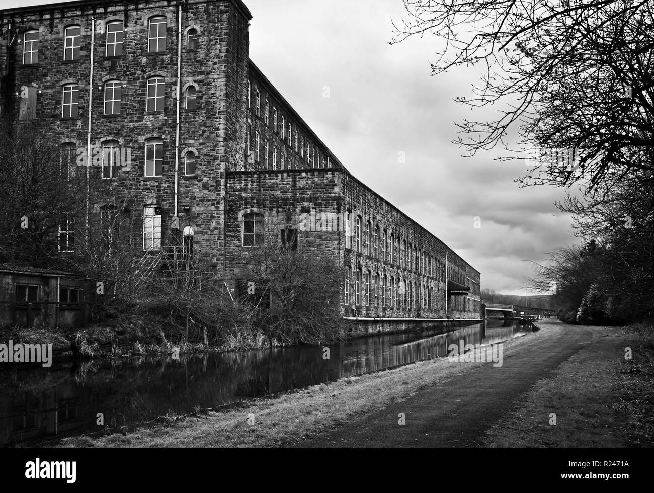 Reminiscent of dark satanic mills: Tunstill Mill, by the Leeds and Liverpool Canal, Brierfield - Stock Image