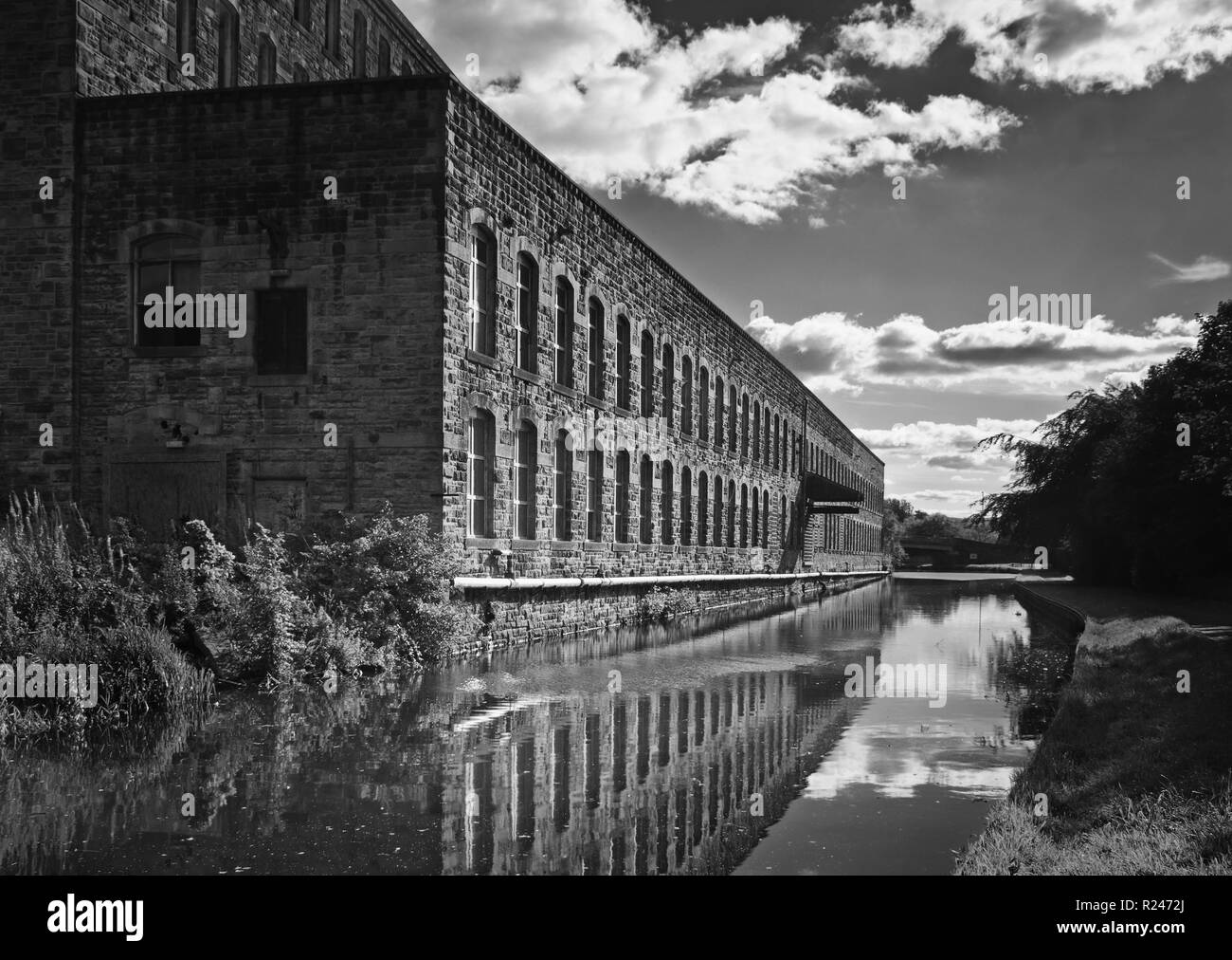 Reflections of industrial glory, at Tunstill Mill, adjacent to the Leeds and Liverpool Canal, Brierfield - Stock Image