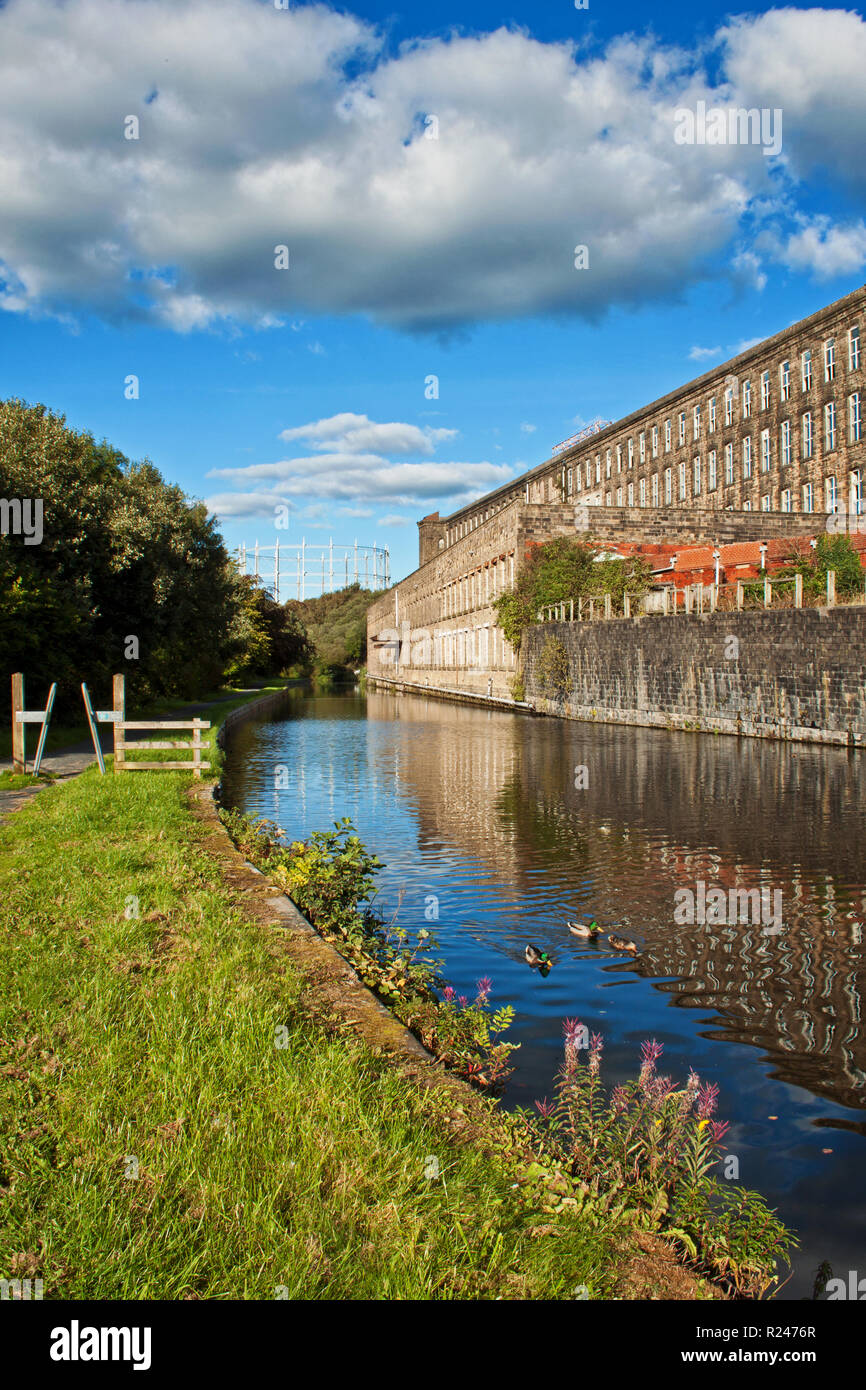 The Leeds and Liverpool canal passes Tunstill Mill at Brierfield, Lancashire - Stock Image