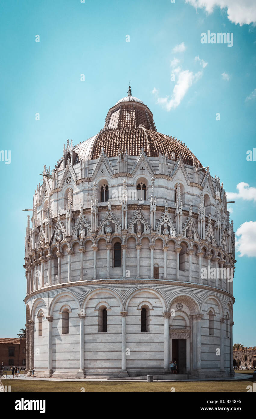 Vertical photo with famous babtistry Battistero di San Giovanni in Pisa. Building is on square Piazza dei Miracoli with leaning tower. Sky is light bl Stock Photo