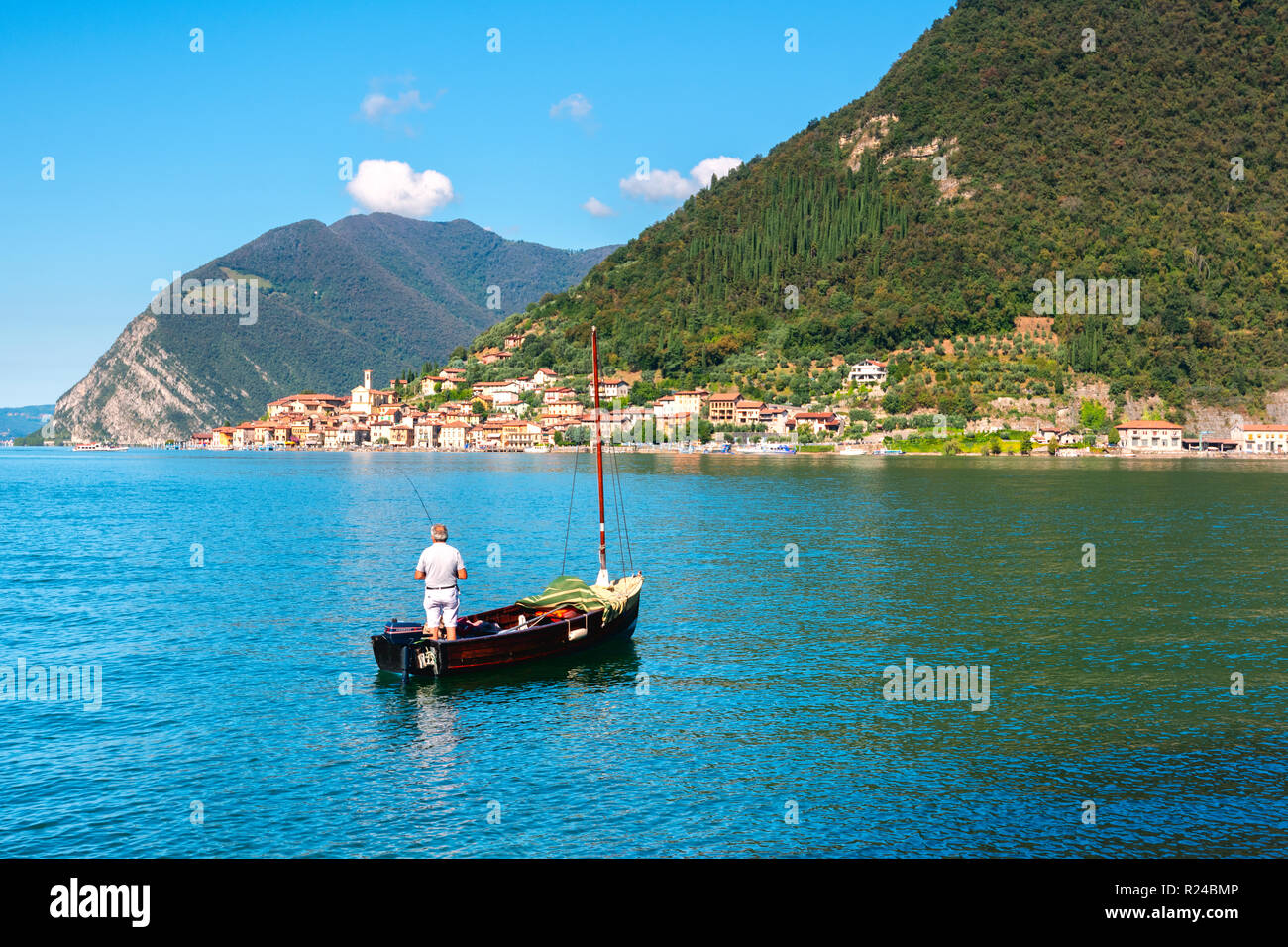 Fisherman with a view of Peschiera Maraglio, Monte Isola, the largest lake island in Europe, Province of Brescia, Italy, Europe - Stock Image