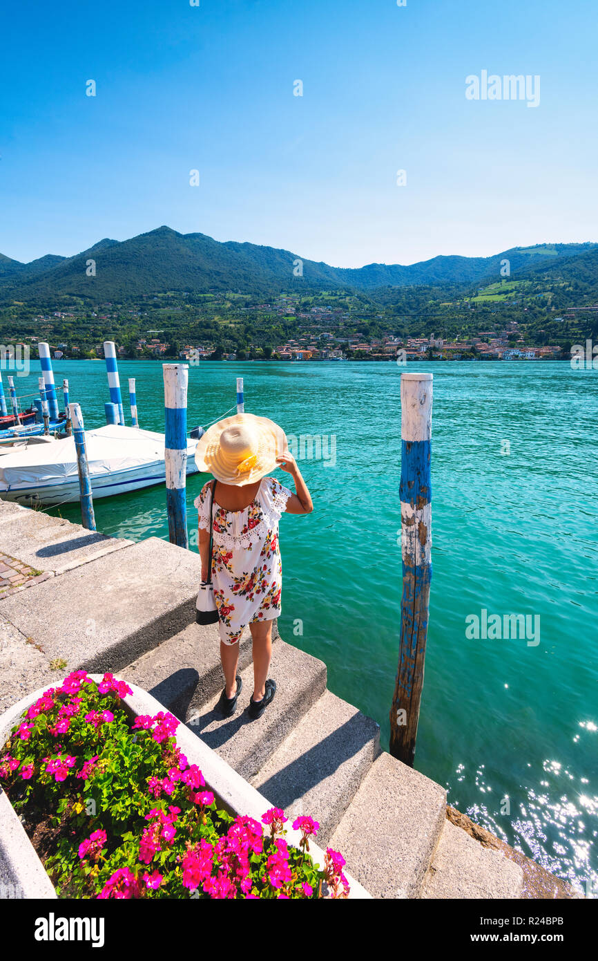 Woman admiring the Iseo Lake seen from Monte Isola, the largest lake island in Europe, Province of Brescia, Lombardy, Italy, Europe - Stock Image