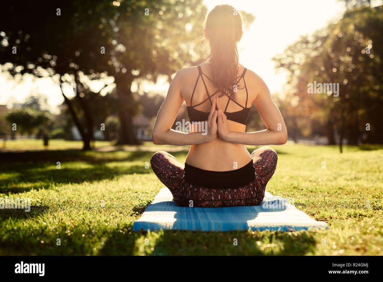 Woman doing yoga at park, reverse prayer position. Fitness woman doing Pashchima Namaskarasana yoga sitting on mat at the park. Rear view shot of fema - Stock Image