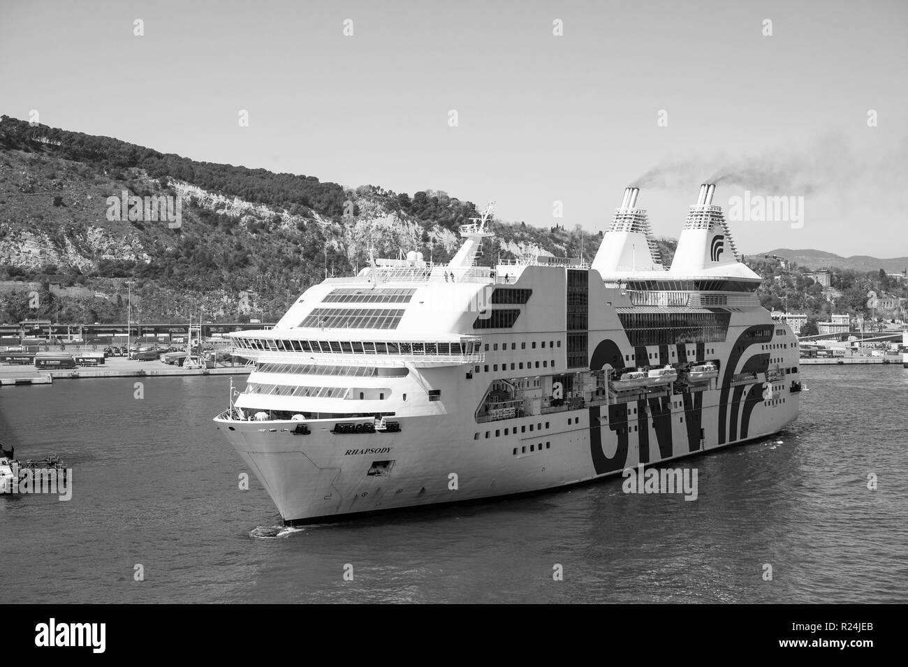 Barcelona, Spain - March 30, 2016: passenger ship GNV Rhapsody Genova in harbor on mountain landscape. Cruise destination and trip. Summer vacation holiday. Wanderlust. Travelling by sea. - Stock Image